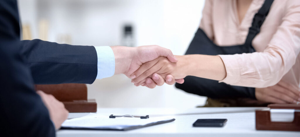 Injured worker shaking hands with insurance agent