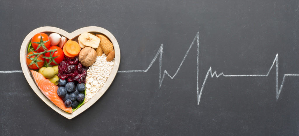 heartbeat pattern drawn on chalkboard with heart-shaped bowl filled with healthy food