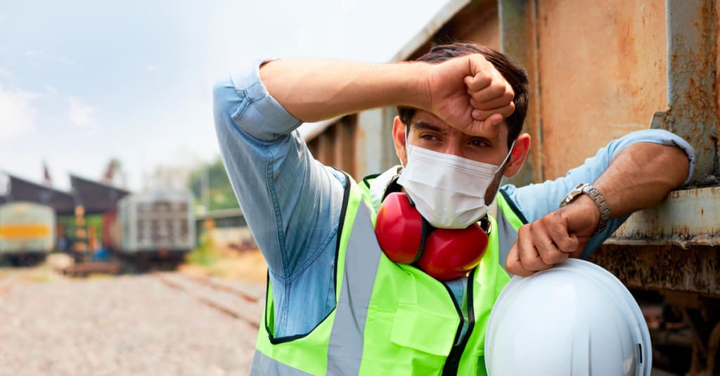 Construction worker pausing to wipe brow on a hot day.