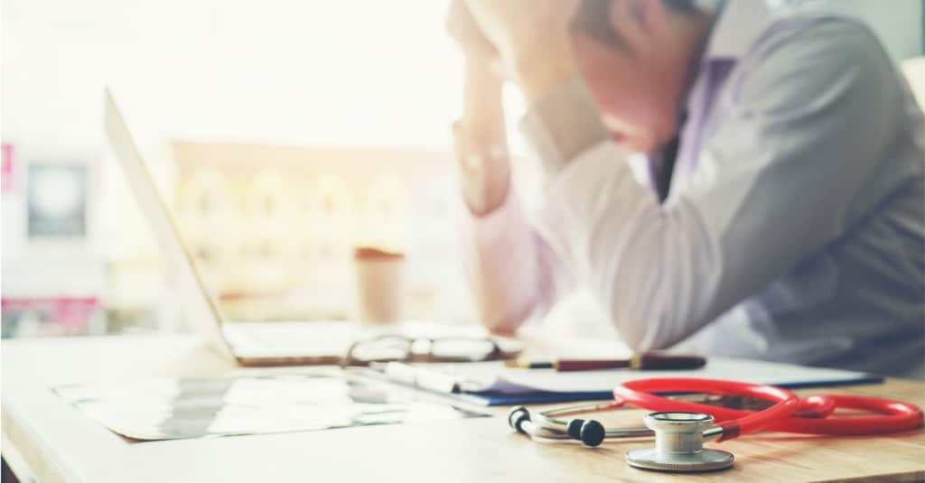 workplace burnout, doctor at desk with head in hands